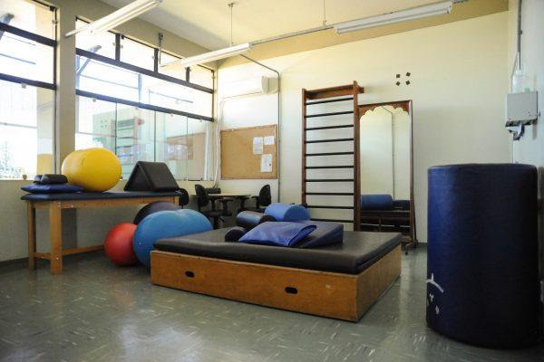 Sala de reabilitação com diversos equipamentos e aparelhos.