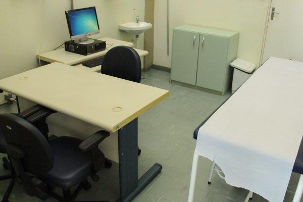 Sala de atendimento com maca e computador.