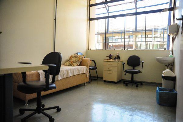 Sala de atendimento psicológico, há um divã, uma mesa e pia.
