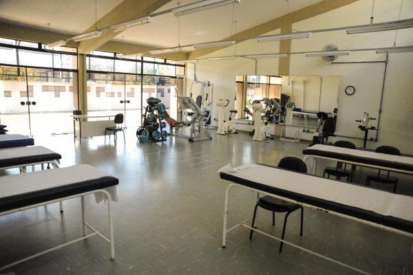 Ginásio multidisciplinar com equipamentos de musculação e macas.
