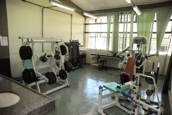 Sala com equipamentos de musculação e anilhas de peso.
