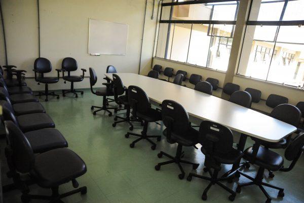 Sala de reunião com uma mesa grande e diversas cadeiras com uma lousa para pincel anatômico.