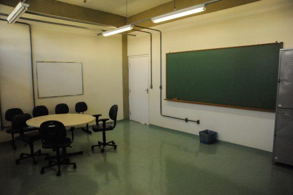 Sala de reuniões com uma mesa pequena e cadeira e uma lousa de giz.