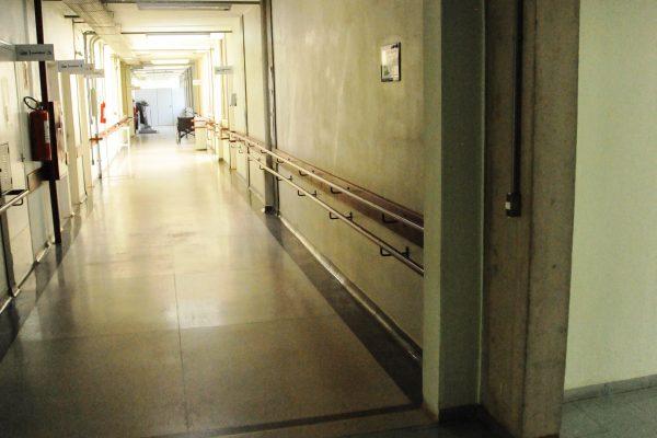 Foto panorâmico do corredor de acesso ao bloco. Ele tem corrimão em toda a extensão.