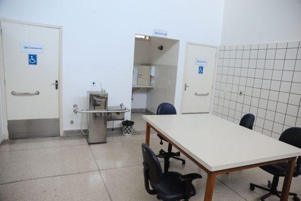 Oficina ortopédica com dois banheiros PCD, um bebedouro e uma mesa.