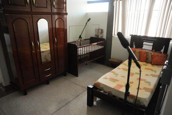 Ambiente de Vida Diária. Quarto com quarta-roupa, berço e cama de solteiro.