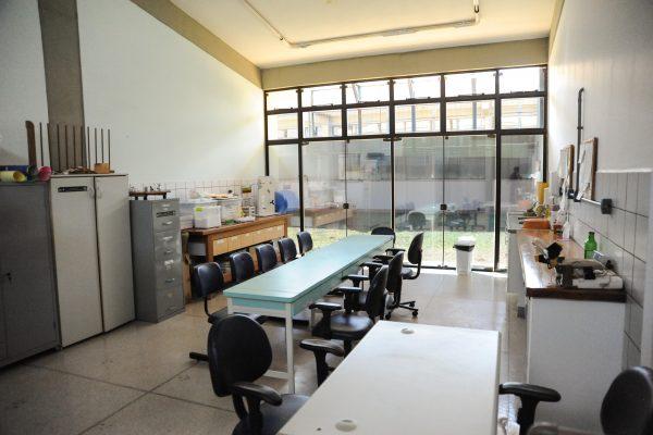 Sala com uma mesa, armários, bancada, um arquivo de documentos e uma pia.