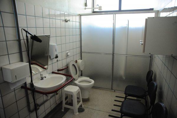 Ambiente de Vida Diária. Banheiro com pia, espelho, armário e chuveiro com box.