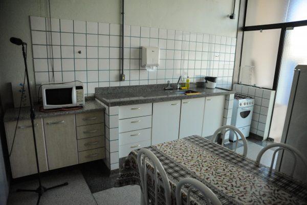 Ambiente de Vida Diária. Cozinha com mesa, fogão, geladeira e pia.