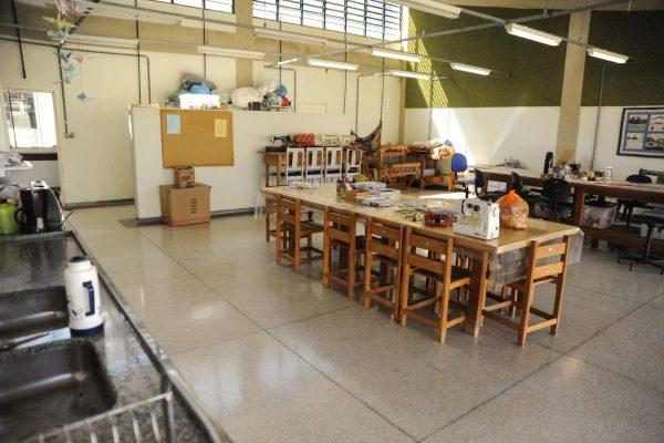 Oficina de atividade manuais. Sala grande com mesa, pia e diversos acessórias como tecidos, linhas e agulhas.