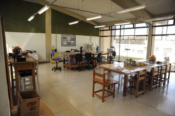 Oficina de atividade manuais. Sala grande com mesa, pia e diversos acessórias como tecidos, linhas e agulhas exibida de outro ângulo.