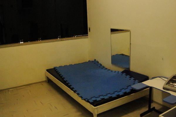 Sala de atendimento interdisciplinar com espelho e uma estrutura com colchonete.